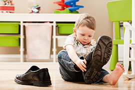Boy (2-3) putting on dad's shoes