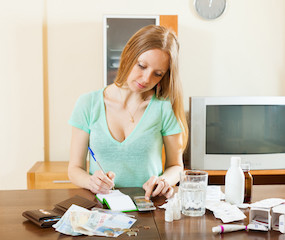 serious woman counting the cost of medications